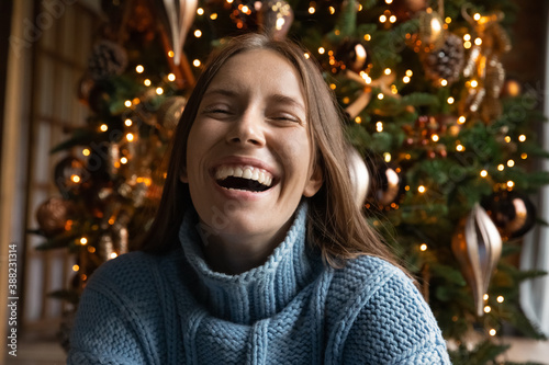 Foto Close up portrait of overjoyed young Caucasian woman have fun laugh and joke enjoying Christmas winter holidays at home
