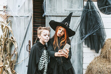 A Boy In A Skeleton Costume And A Girl In A Witch Costume Takes A Selfie At A Halloween Party On The Decorated Porch