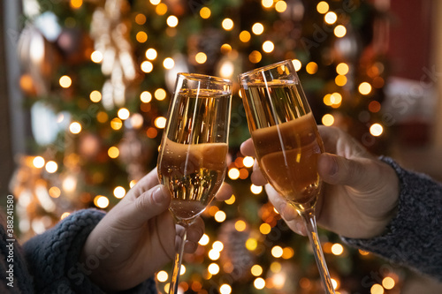 Crop close up of man and woman hold glasses with champagne clink greet congratulate with New Year Billede på lærred