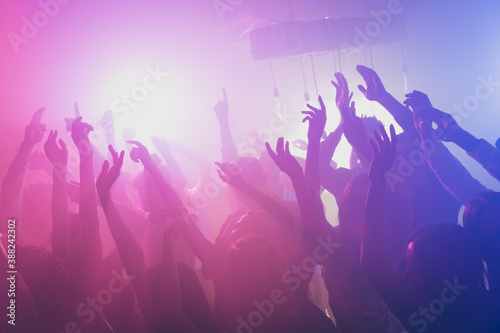 Photo of big group many people funky event stage dj concert neon bright pink spo Fotobehang