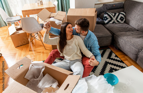 Fotografie, Obraz Smiling young couple move into a new home sitting on floor and unpacking boxes of their belongings
