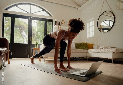 Foto Young woman following video on laptop while exercising on yoga mat at home