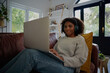 Portrait of african woman sitting using laptop watching video with headphones on couch