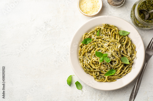 Fotografering Spaghetti pasta with pesto sauce, parmesan cheese and basil leaves in plate on c