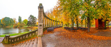Panorama Over Lonely Empty Benches Under Old Chestnut Trees And Old Columns With Fallen Red And Orange Leaves In The City Park In Autumn Colors In Rainy Day, Magdeburg, Germany.