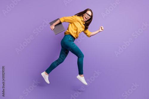 Full length profile photo of lady jump run hold netbook wear yellow shirt blue pants sneakers isolated purple color background