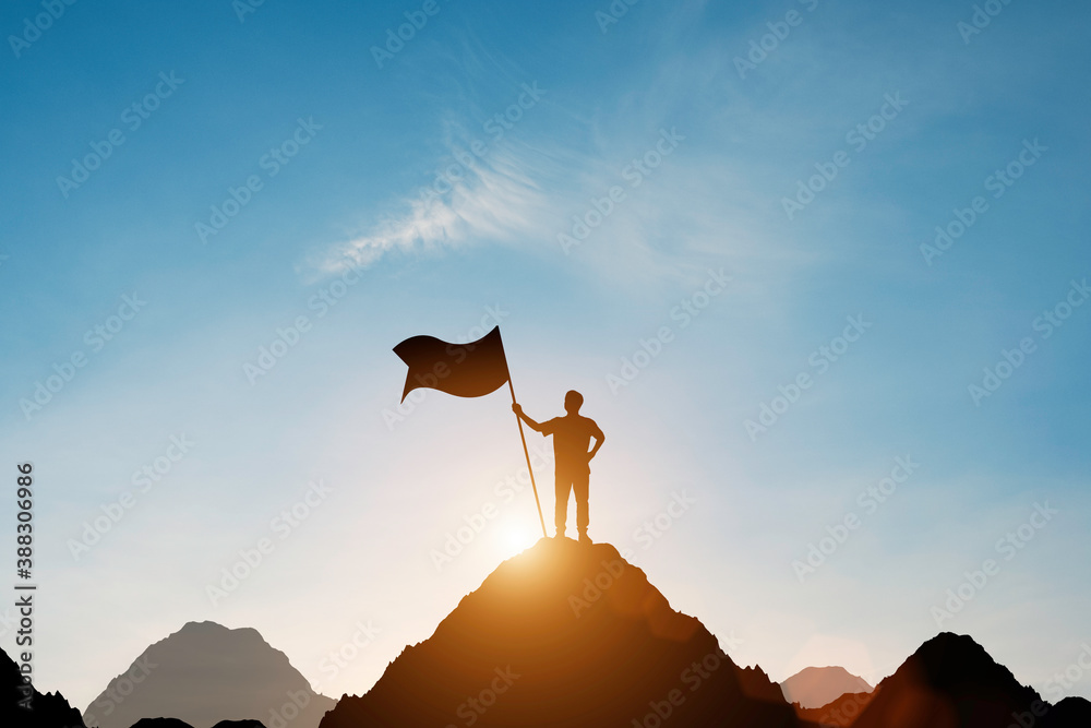 Fototapeta Silhouette of businessman holding flag on the top of mountain with over blue sky and sunlight. It is symbol of leadership successful achievement with goal and objective target.