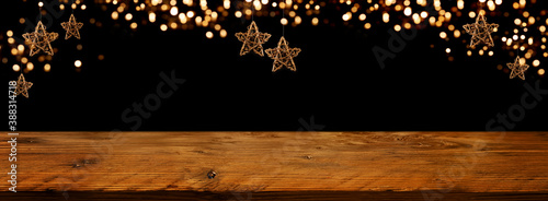 Photo Golden Christmas stars with festive bokeh lights in front of illuminated rustic wooden table