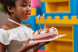 Africa American children hold on celebrating her birthday cake and blow candles on cake in Kids birthday celebratiion party.