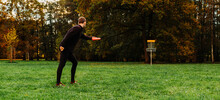 Young Caucasian Man Playing Disc Golf On Autumn Play Course With Basket
