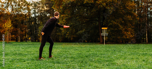 Photo Young caucasian man playing disc golf on autumn play course with basket