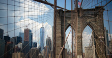 Brooklyn Bridge With Modern Buildings On The Other Side Of The Steel Mesh.