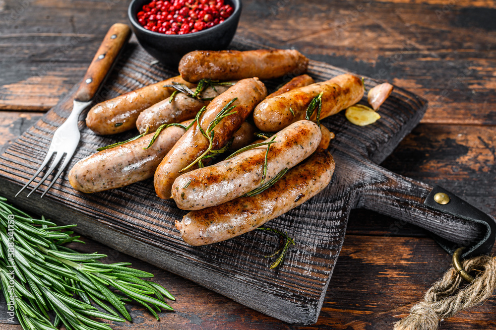 Fototapeta Grilling bavarian sausages on a cutting board. Dark wooden background. Top view