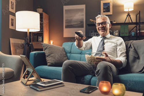 Fotografia Businessman relaxing on the sofa and watching tv