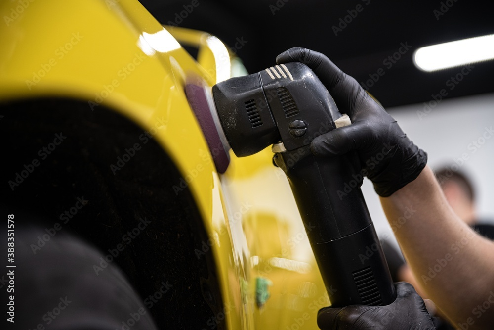 Fototapeta Man car detailing studio worker polishing yellow car varnish with electrical polisher