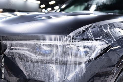 Obraz Car detailing specialist installing protective transparent foil - fototapety do salonu
