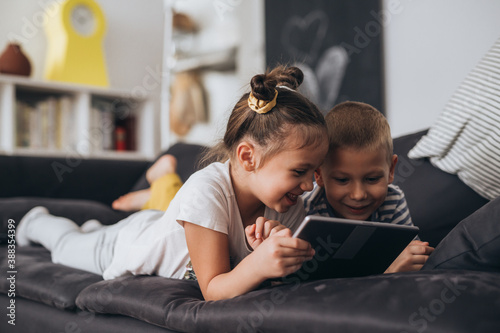 Fotografie, Obraz brother and sister laying on sofa and using tablet computer at home