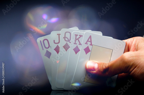 Fotografía Man's hand holding a royal flush while playing a winning game at poker