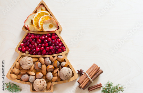 Fotografering Nuts, cranberries and dried fruit in Christmas tree-shaped bowl on light backgro