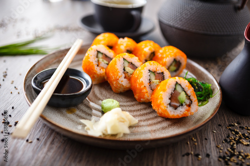 Papel de parede Sushi maki rolls with salmon, avocado, cucumber, flying fish roe on a plate with chopsticks, soy sauce, wasabi and ginger