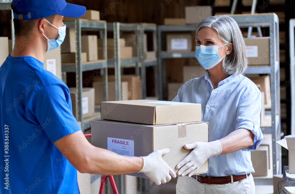 Fototapeta Female manager supervisor wearing face mask preparing fast drop shipping safe delivery giving parcels packages boxes to male courier taking ecommerce orders to deliver standing in warehouse storage.