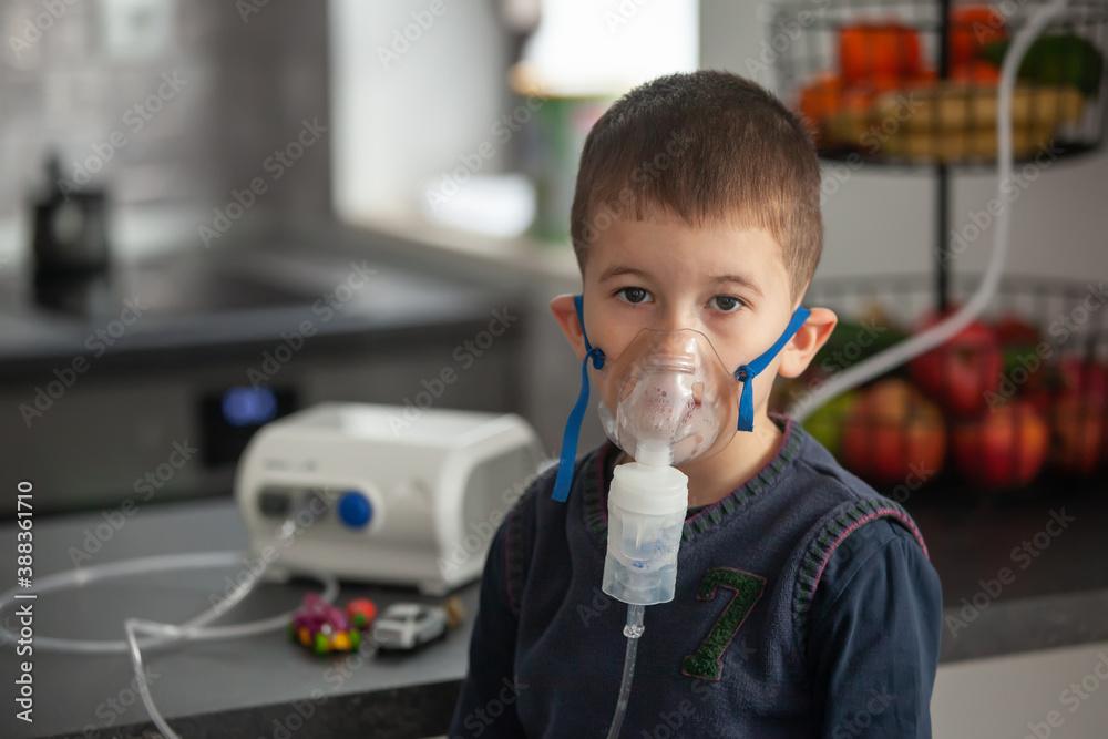 Fototapeta Little boy doing his inhalation with nebulizer at home. Child asthma inhalation nebulizer steam sick cough concept.