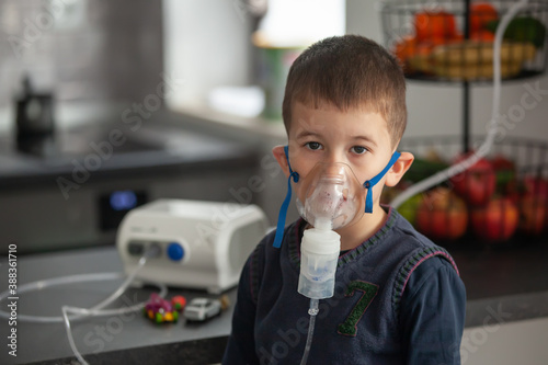 Leinwand Poster Little boy doing his inhalation with nebulizer at home