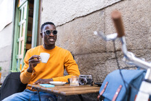 Black Man Drinking Coffee In A Cafe Wearing Sunglasses.