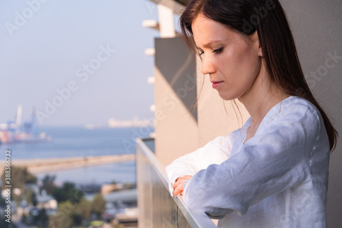 Fotografie, Obraz Beautiful woman on the balcony in the morning watching on city at summer