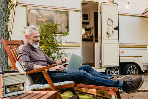 Photographie Attractive grey-haired man resting on the wooden deck chair using laptop with ca
