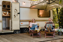 Senior Joyful Couple Relaxing In The Porch Of Thier Motorhome With Book And Laptop