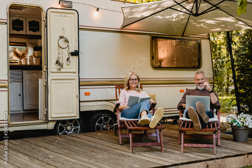 Fotografía Senior joyful couple relaxing in the porch of thier motorhome with book and lapt