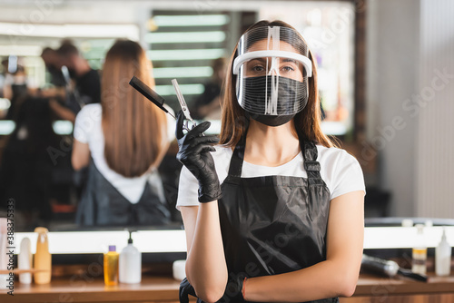 hairdresser in face shield, latex gloves and apron holding comb and scissors on blurred background