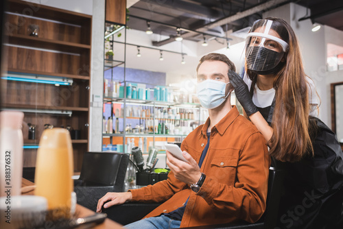 hairdresser in face shield looking at camera near man in medical mask holding smartphone, blurred foreground