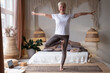 caucasian senior woman in yoga pose vrikshasana, tree pose.