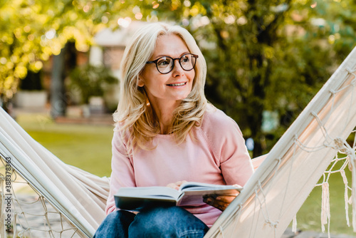 Fototapeta Smiling senior good-looking blond woman wearing glasses while reading in hammock in the summer garden obraz
