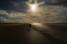 A Silhouette Of A Lady Walking A Dog On Silloth Beach In Cumbria