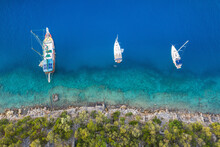 Three Sail Boats Staying On Anchor Parking Close To The Rock Coast In Calm Emerald Water