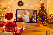 Little Kid Video Calling Father Christmas And Waving Hand At Screen Sitting In Cozy Room At Home