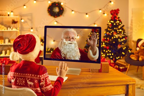 Fotografie, Obraz Little kid video calling Father Christmas and waving hand at screen sitting in c
