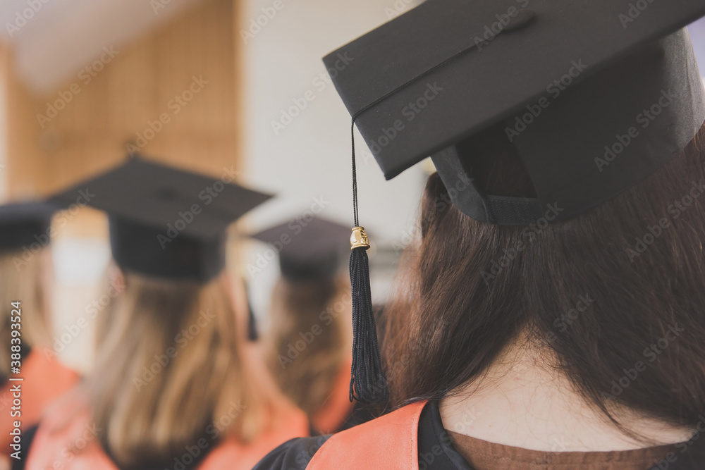 Fototapeta Women graduates of the university in square academic caps with tassel during graduation ceremony