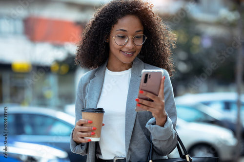 Slika na platnu Pretty young business woman using her smart phone while drinking coffee walking down the street