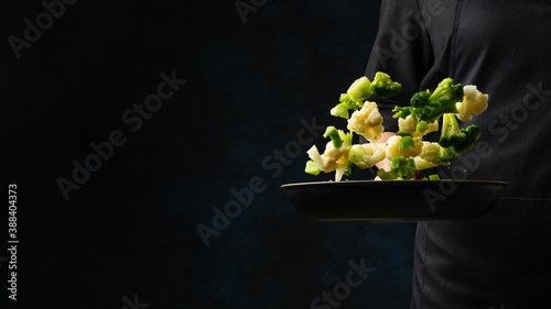 Tela Professional chef in black uniform throws up frying mix of cabbage and broccoli above the pan on dark blue background