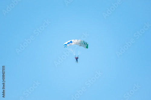 Fotografie, Obraz one parachutist floats slowly at low altitude on the background of clear sky