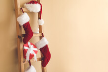 Ladder With Christmas Gift, Santa Hat And Socks Near Color Wall