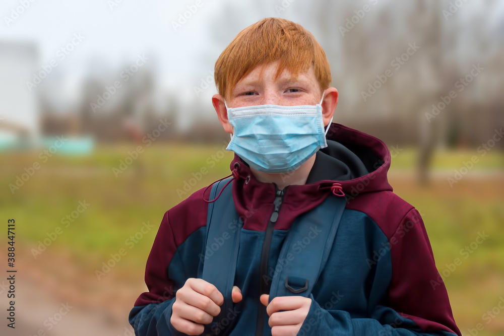 Fototapeta A student, adolescent red-haired boy in a protective medical mask, goes to school during the covid-19 virus pandemic.