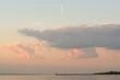 Krajobraz molo i widok nieba podświetlonego zachodzącym słońcem z chmurami i śladem na niebie po przelatującym samolocie