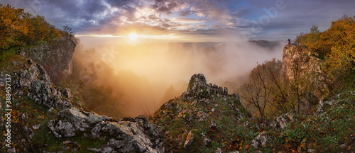 Dramatic sunrise in mountains with fog, sun and silhouette of man - landcape pan Canvas Print