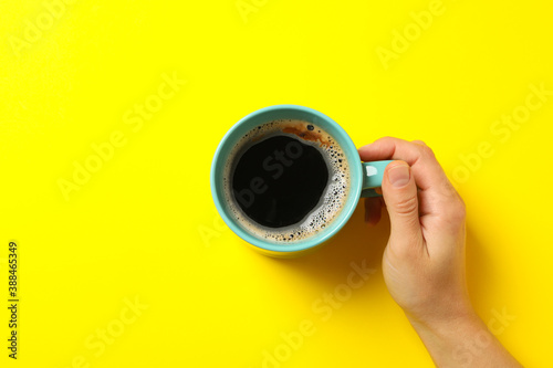 Female hand hold cup of coffee on yellow background Canvas