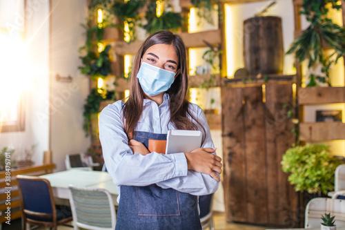 Slika na platnu Happy female waitress using digital tablet while wearing protective face mask at the restaurant or cafe